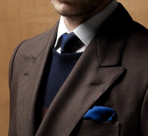 Man in brown sports coat and navy blue sweater vest, pocket square and tie